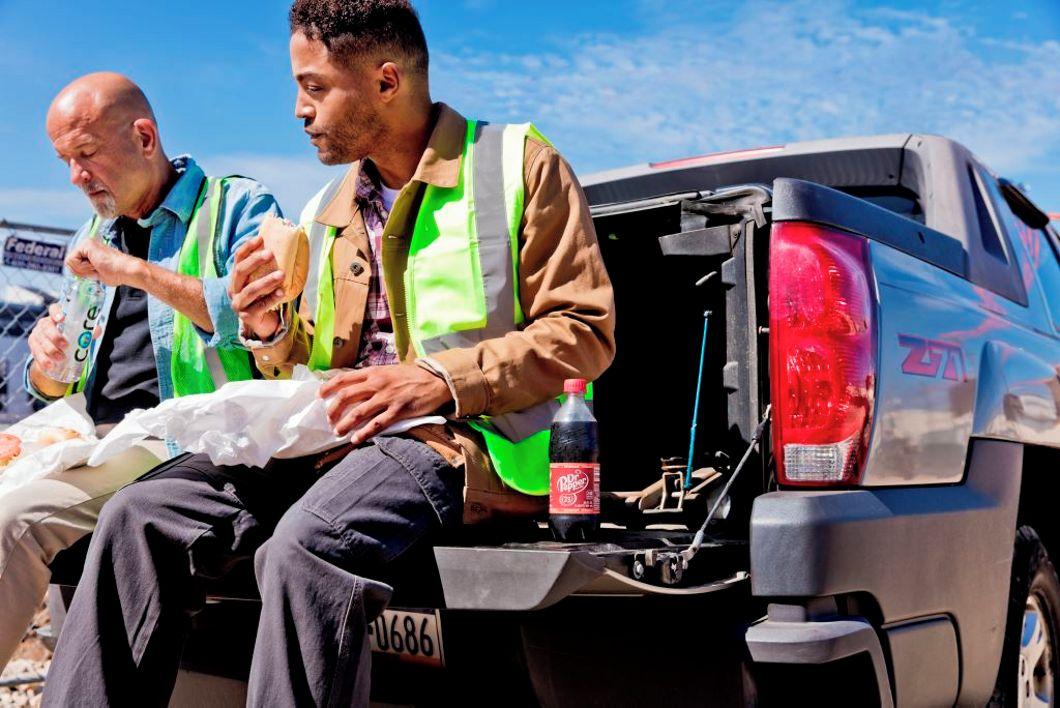 Men eating sandwiches on the trucks