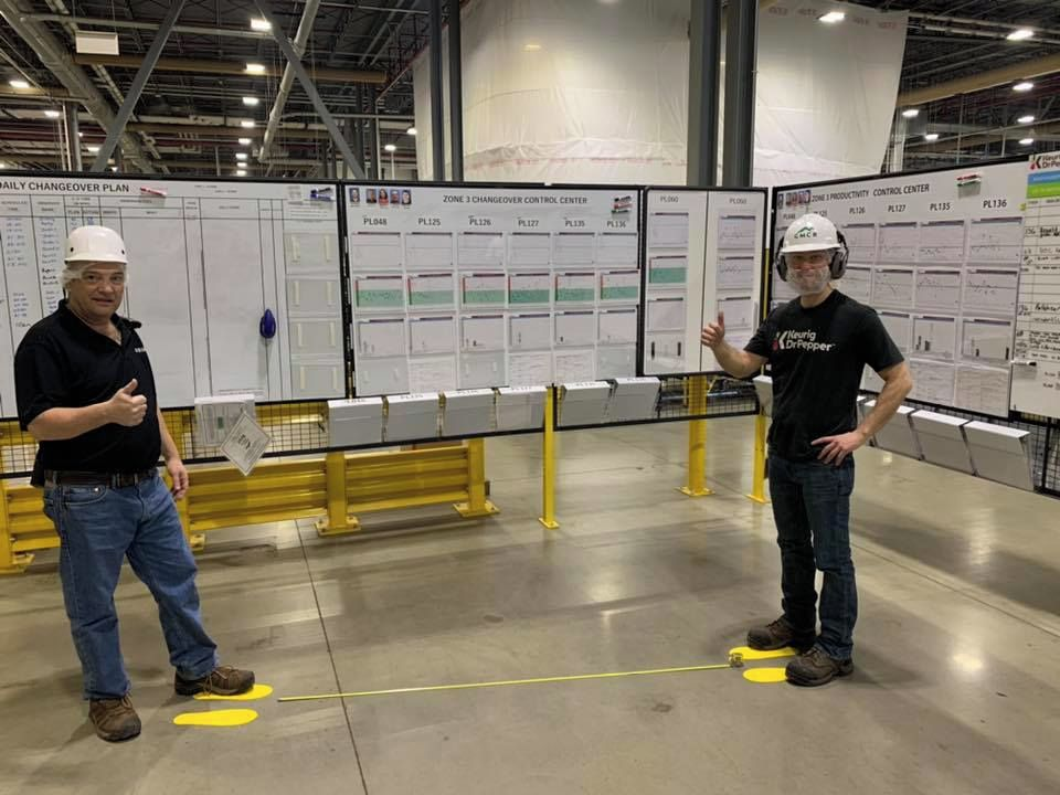 Warehouse workers stand in front of schematics.